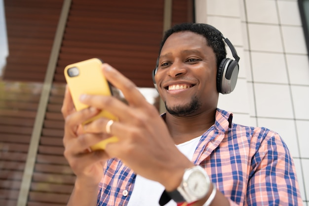 African american man using his mobile phone while standing outdoors on the street
