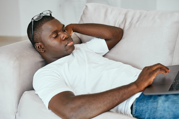 African american man using the laptop in the sofa