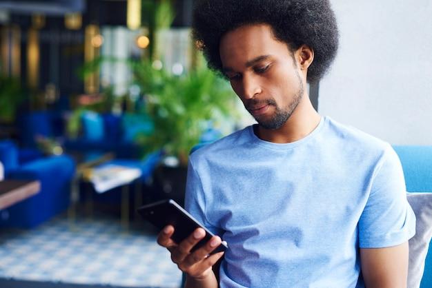 Uomo afroamericano che usa un telefono cellulare