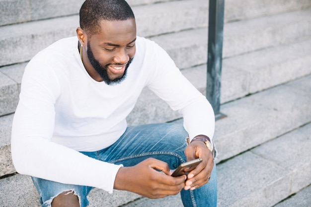 African-american man using smartphone on stairs