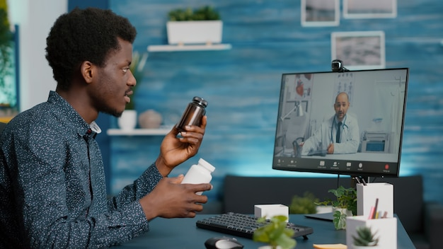 African american man in video conference call with his doctor using medical internet app for healthc...
