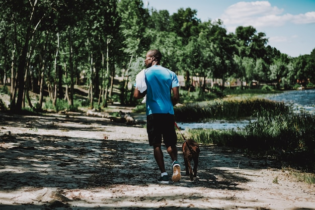 African american man walking dog by river.