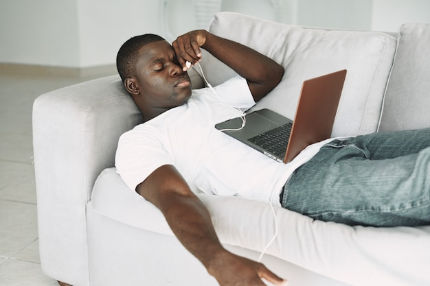 African american man watching a film on laptop, resting on the sofa