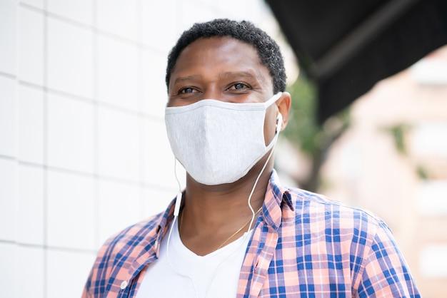 Афро-американский мужчина в маске для лица во время прослушивания музыки в наушниках на открытом воздухе на улице.