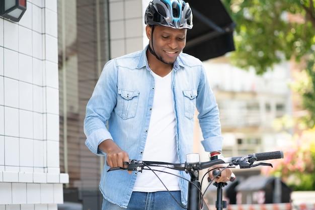 거리에서 자전거와 함께 걷는 동안 헬멧을 착용하는 아프리카 계 미국인 남자