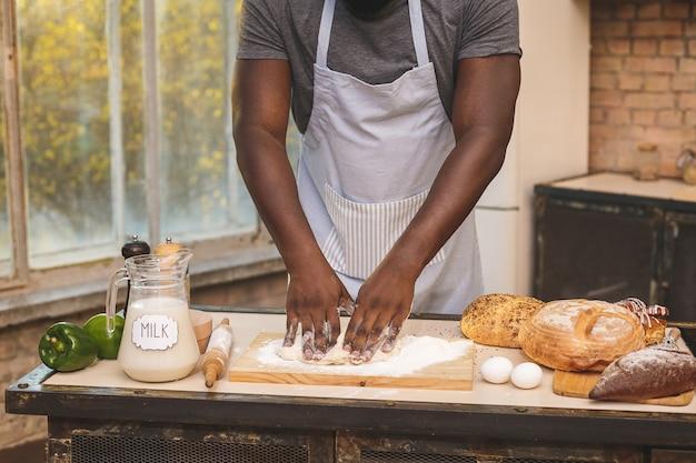 Афро-американский мужчина в фартуке и выпечки