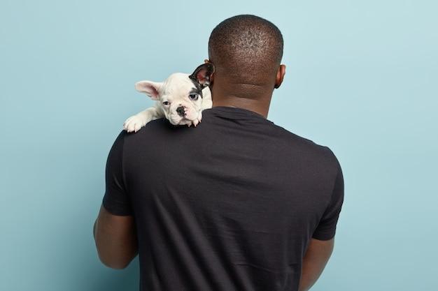 黒のtシャツを着て、小さな犬を保持しているアフリカ系アメリカ人の男