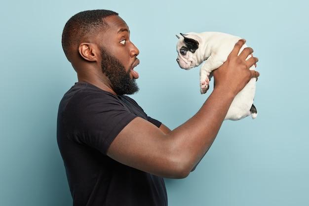 Афро-американский мужчина в черной футболке и держит собачку
