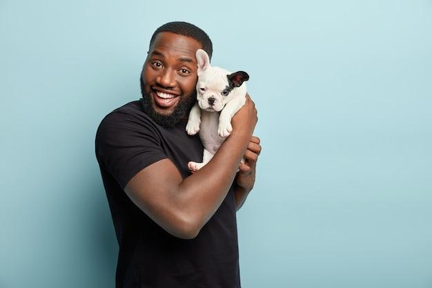 검은 티셔츠를 입고 작은 개를 들고 아프리카 계 미국인 남자