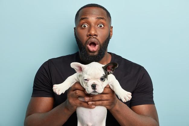 Uomo afroamericano che indossa la maglietta nera e che tiene piccolo cane