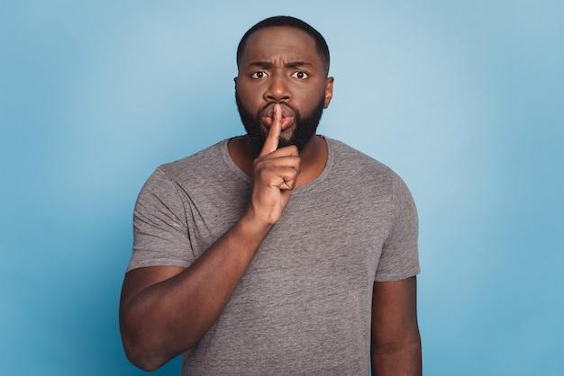 唇に指で静かにすることを求めるカジュアルな服を着ているアフリカ系アメリカ人の男