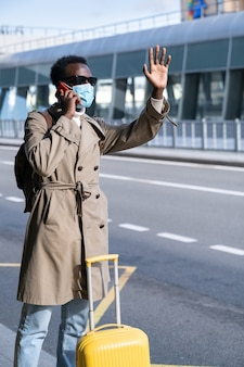 African american man wearing face mask next to airport