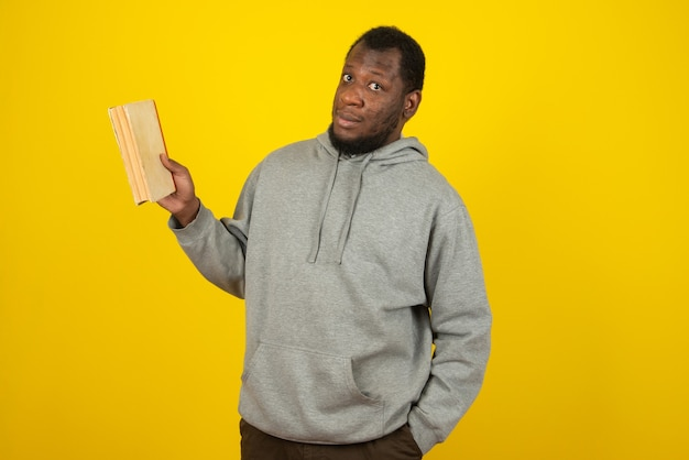 灰色のスウェットシャツを着て、片方の手に本を、もう片方の手にポケットを持ったアフリカ系アメリカ人の男性が、黄色い壁の上に立っています。