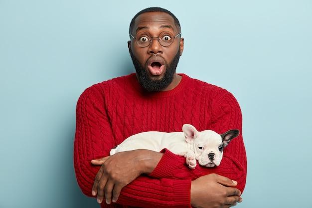 Афро-американский мужчина в красном свитере и держит собачку