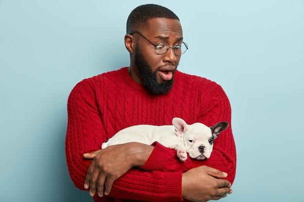 赤いセーターを着て、小さな犬を保持しているアフリカ系アメリカ人の男