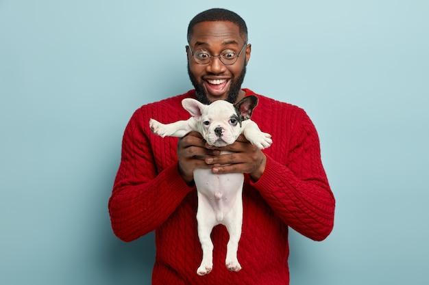 빨간 스웨터를 입고 작은 개를 들고 아프리카 계 미국인 남자