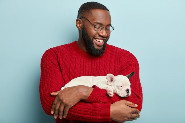 犬を保持している赤いセーターを着ているアフリカ系アメリカ人の男