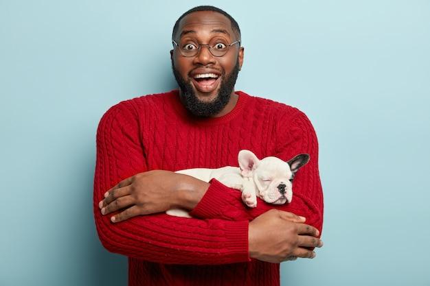 Афро-американский мужчина в красном свитере держит собаку