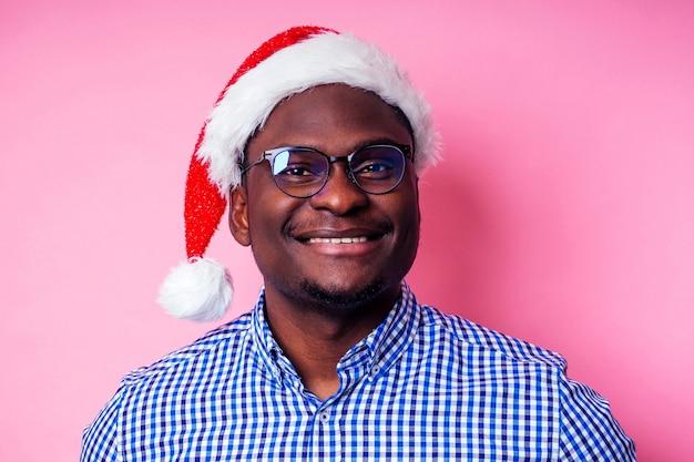 Афро-американский мужчина в стильной клетчатой рубашке с большой улыбкой в новогодней шапке с подарочной коробкой на розовом фоне студии. темнокожий санта-клаус поздравляет с рождеством