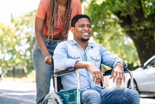 Un uomo afroamericano su una sedia a rotelle che si gode una passeggiata all'aperto con la sua ragazza