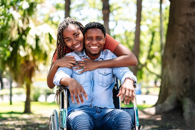 An african american man in a wheelchair enjoying a walk at the park with his girlfriend.
