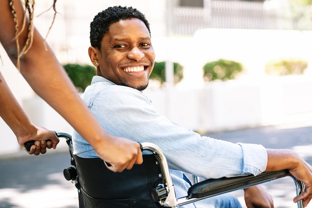 An african american man in a wheelchair smiling and looking at the camera while his girlfriend pushing him.
