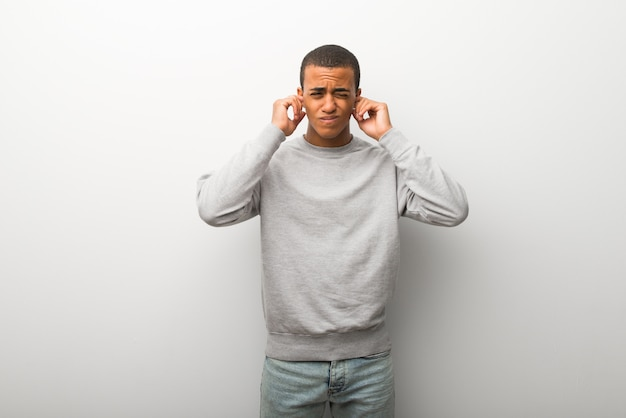 African american man on white wall background covering ears with hands. frustrated expression