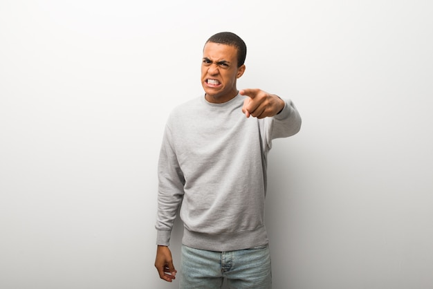 African american man on white wall background frustrated by a bad situation and pointing to the front