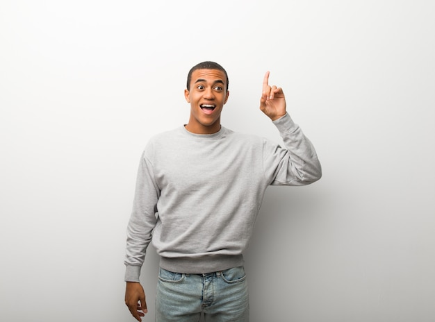 African american man on white wall background intending to realizes the solution while lifting a finger up