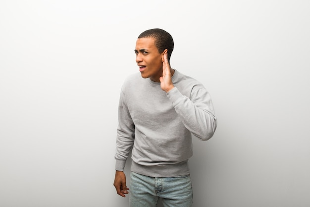 African american man on white wall background listening to something by putting hand on the ear