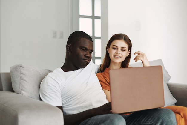 African american man and white woman couple using laptop in the sofa