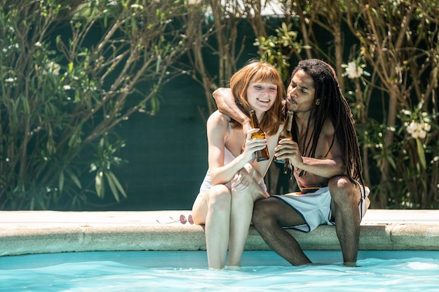 African-american man and white woman toasting with beer bottles on the edge of a pool.