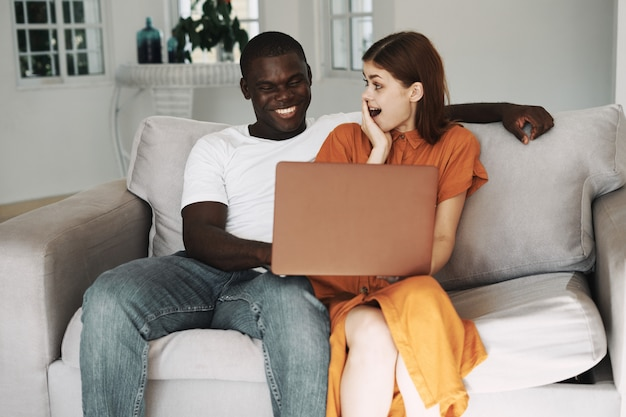African american man and white woman working at home freelancer laptop, couple