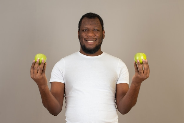 Афро-американский мужчина с яблоком в обеих руках, стоящий перед серой стеной.