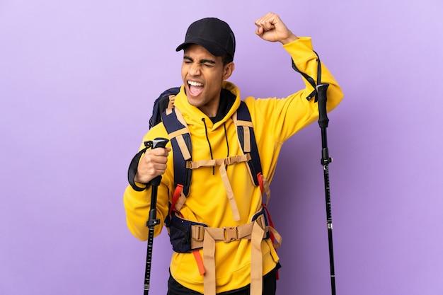 勝利を祝う孤立した壁を越えてバックパックとトレッキングポールを持つアフリカ系アメリカ人の男