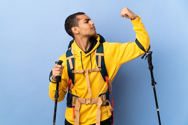 African american man with backpack and trekking poles over isolated background doing strong gesture