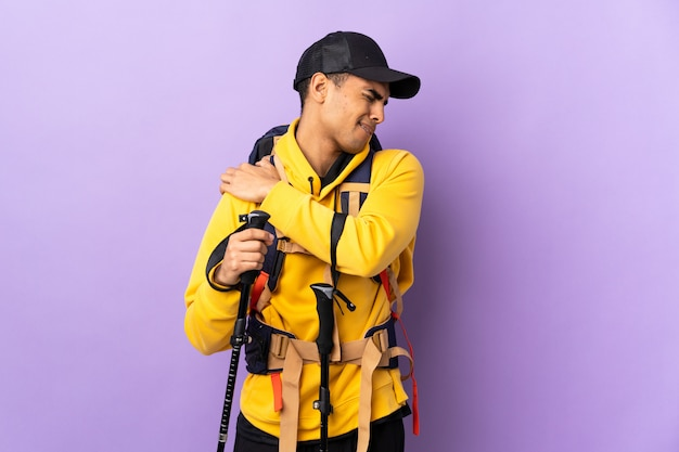 African american man with backpack and trekking poles over isolated wall suffering from pain in shoulder for having made an effort
