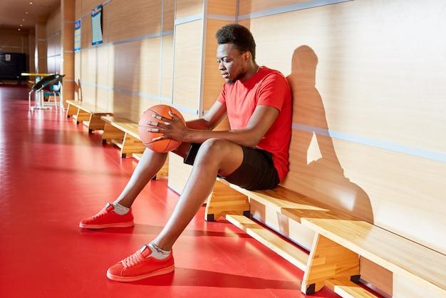 Афро-американский мужчина с баскетбольным мячом на скамейке