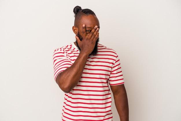 ピンクの背景に分離されたひげを持つアフリカ系アメリカ人の男は、恥ずかしい顔を覆って、指を介してカメラで点滅します。