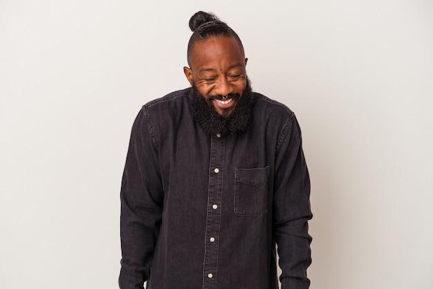 ピンクの背景に分離されたひげを持つアフリカ系アメリカ人の男は笑って目を閉じ、リラックスして幸せを感じます。