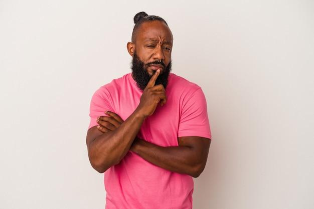 분홍색 배경에 격리된 수염을 기른 아프리카계 미국인 남자는 의심스럽고 회의적인 표정으로 옆을 바라보고 있습니다.