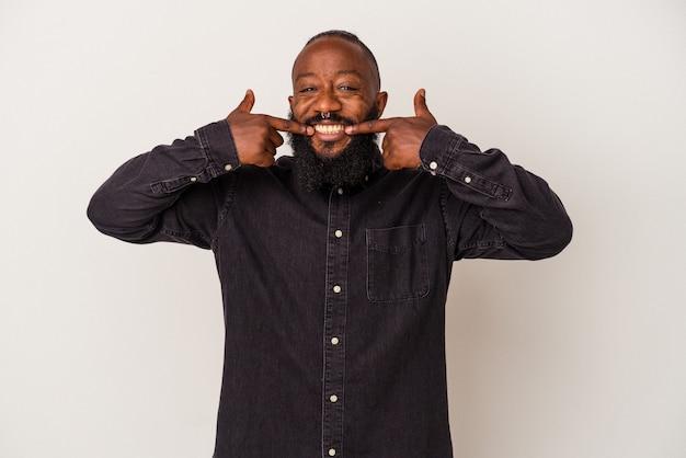 분홍색 배경에 고립 된 수염을 가진 아프리카 계 미국인 남자는 입에 손가락을 가리키는 미소.