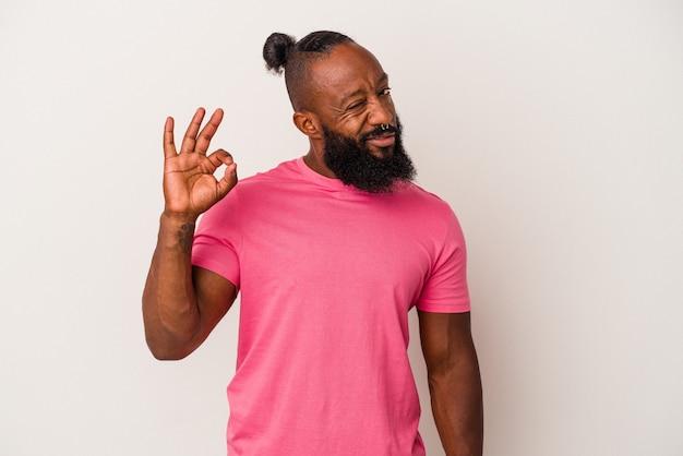 분홍색 배경에 격리된 수염을 기른 아프리카계 미국인 남자는 눈을 윙크하고 손으로 괜찮은 몸짓을 합니다.