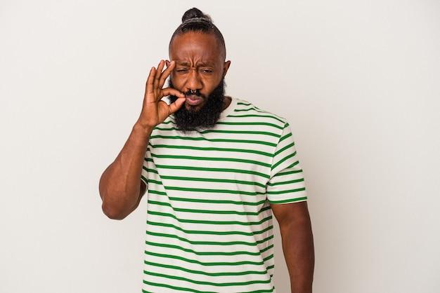 비밀을 유지 하는 입술에 손가락으로 분홍색 배경에 고립 된 수염을 가진 아프리카계 미국인 남자.