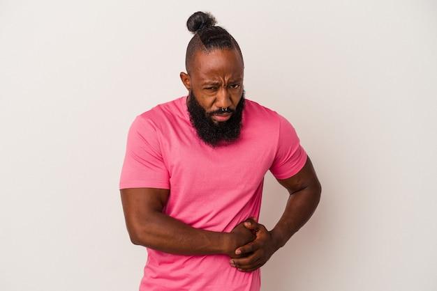 ピンクの壁に孤立したひげを持つアフリカ系アメリカ人の男性は、肝臓の痛み、胃の痛みを持っています。