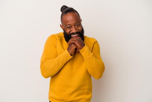 Афро-американский мужчина с бородой, изолированные на розовой стене, держит руки под подбородком, счастливо смотрит в сторону.