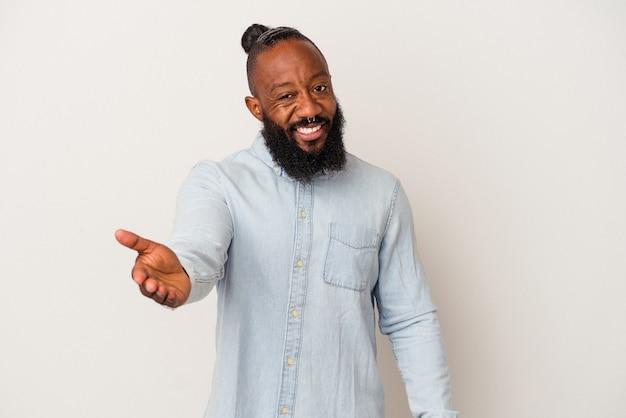 挨拶のジェスチャーで手を伸ばすピンクの壁に分離されたひげを持つアフリカ系アメリカ人の男。
