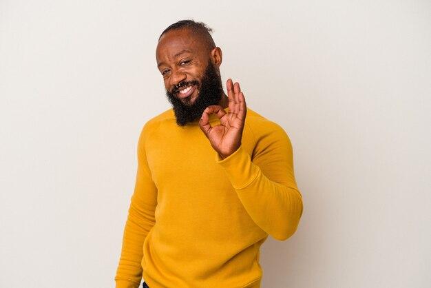 분홍색 벽에 고립 된 수염을 가진 아프리카 계 미국인 남자는 눈을 윙크하고 손으로 괜찮아 제스처를 보유하고 있습니다.