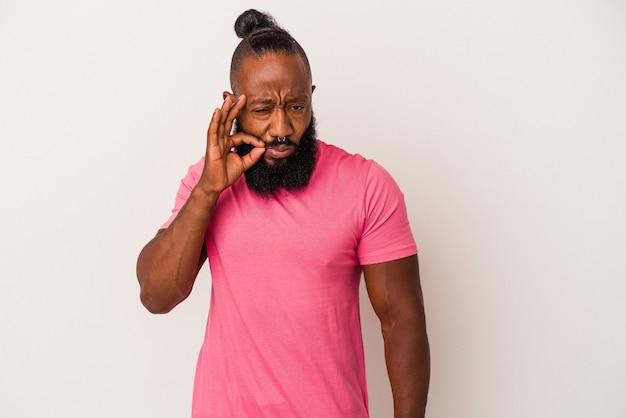 비밀을 유지하는 입술에 손가락으로 분홍색 벽에 고립 된 수염을 가진 아프리카 계 미국인 남자.
