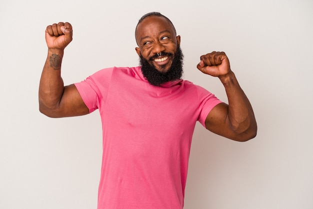 African american man with beard isolated on pink background celebrating a special day, jumps and raise arms with energy.